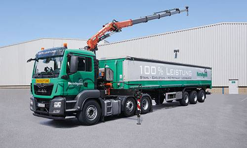 Semi-trailer truck with crane and tarpaulin